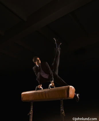 Hispanic business man in a business suit performing on a pommel horse. Black background. His hands are on the handles and his feet and legs are up in the air.